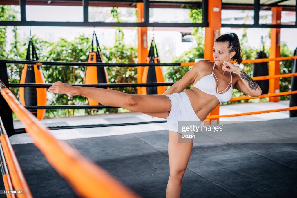 Woman exercising kicking in boxing ring : Stock Photo