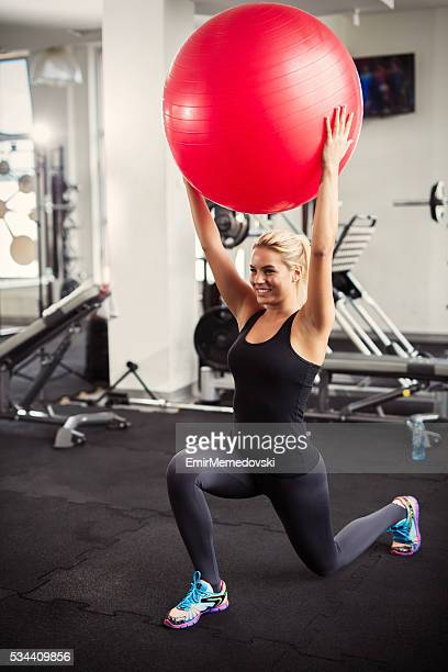 Woman exercising lunges with fitness ball in a health club.