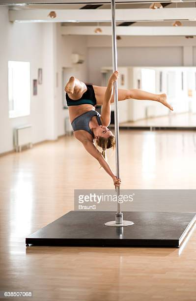 woman exercising on a dancing pole in a studio. - pole dance photos et images de collection