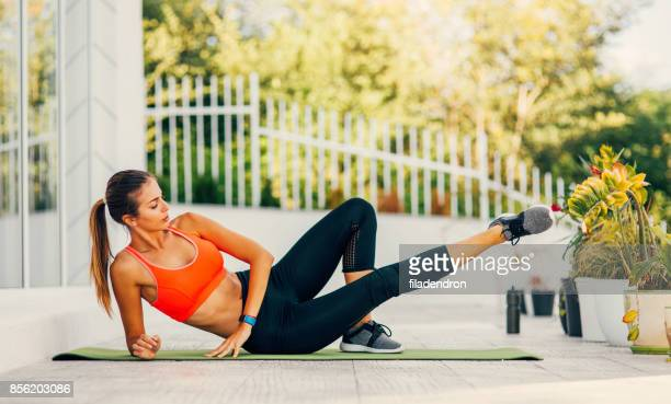 woman exercising on a porch - lying on side stock pictures, royalty-free photos & images