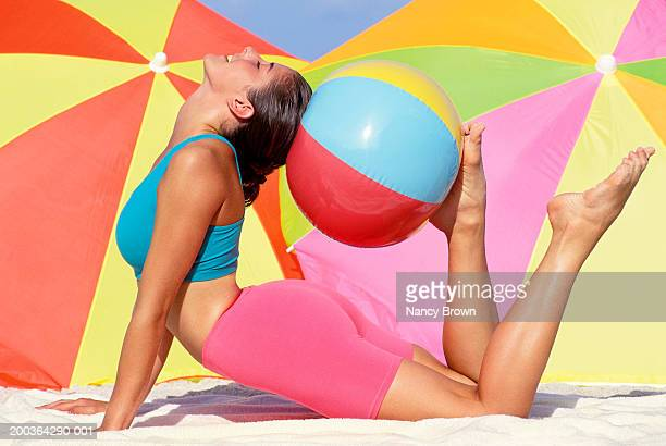 Woman exercising on beach with beach ball, side view