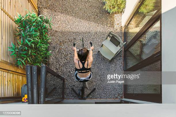 woman exercising on bike at home - elevated view stock pictures, royalty-free photos & images