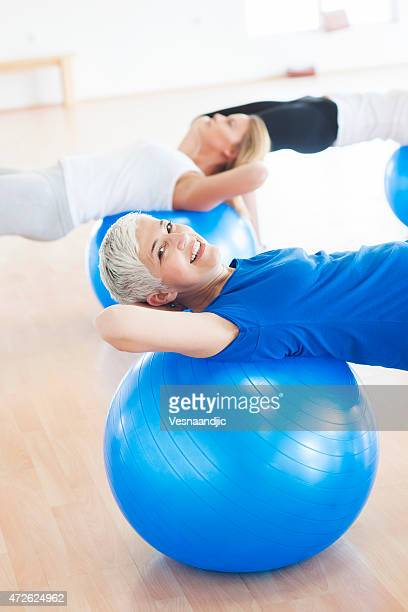 Woman exercising on blue ball in gym