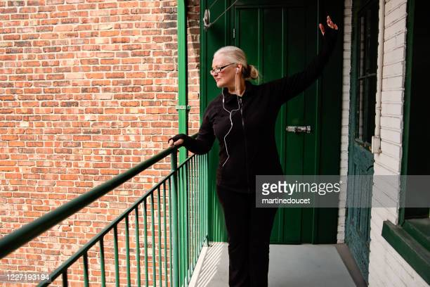 "50+ woman exercising on city balcony. - ""martine doucet"" or martinedoucet stock pictures, royalty-free photos & images"