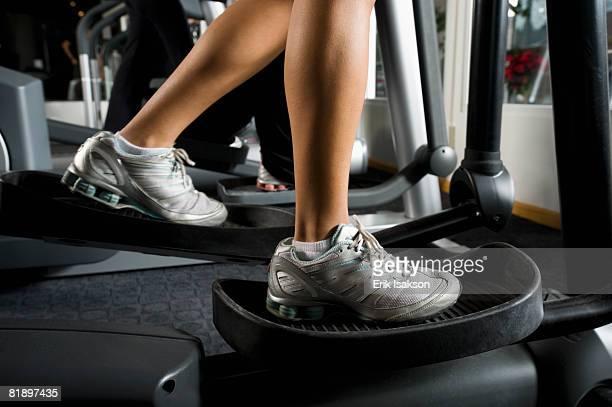 Woman exercising on elliptical machine