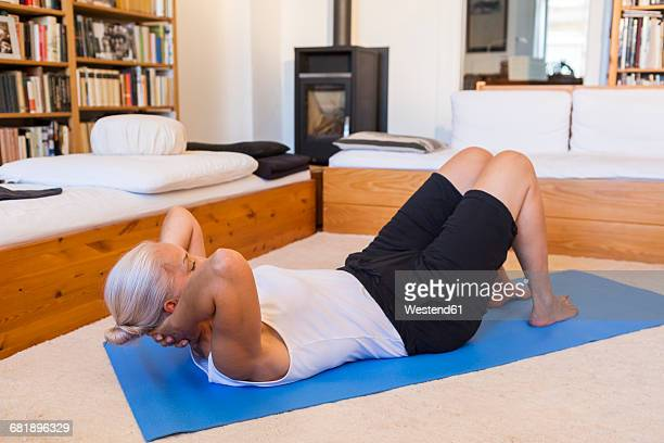 Woman exercising on gym mat in living room