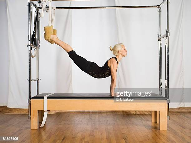Woman exercising on pilates equipment