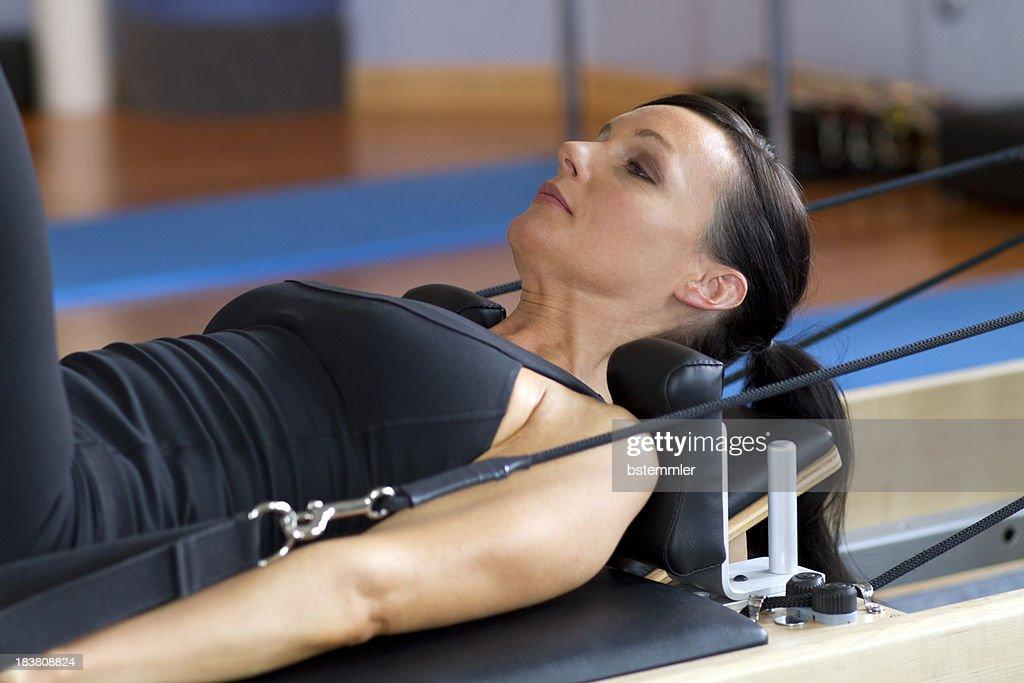 Mulher s'exercitando em com equipamento para Pilates : Foto de stock