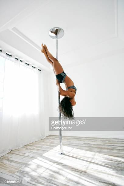 woman exercising on pole - pole dance photos et images de collection