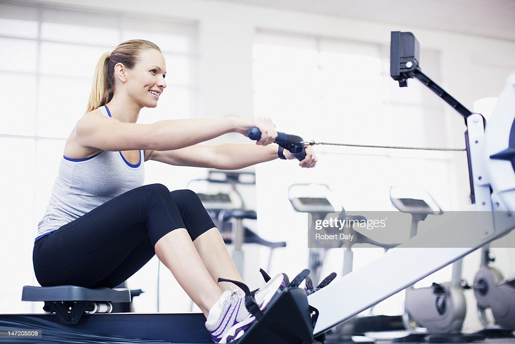 Woman exercising on rowing machine in gymnasium : Stock Photo