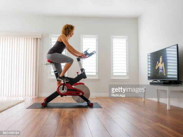 woman exercising on spin bike in home - peloton stock pictures, royalty-free photos & images