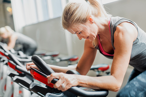 Woman exercising on stationary bicycle in gym - gettyimageskorea