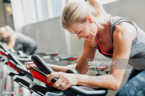 woman exercising on stationary bicycle in gym - spinning stock pictures, royalty-free photos & images