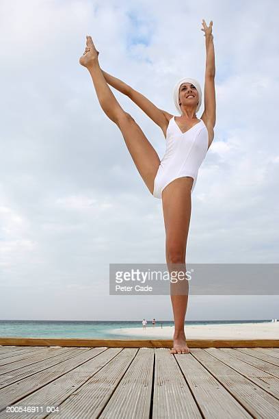 Woman exercising on wooden jetty, smiling