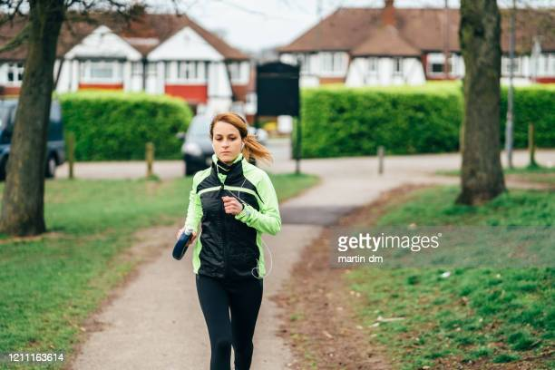 woman exercising outside - females stock pictures, royalty-free photos & images