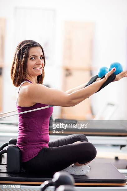 Woman exercising Pilates on a machine with weight balls.