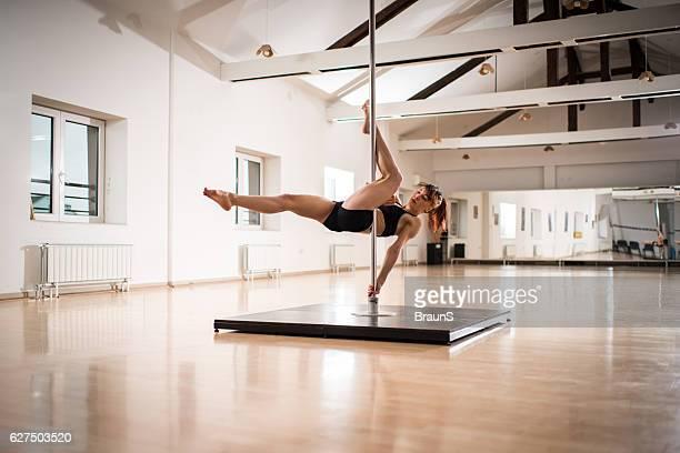 Woman exercising pole dancing in a dance studio.