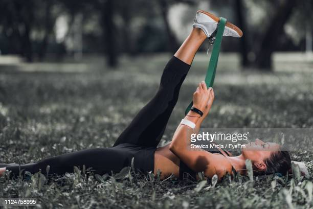 woman exercising while lying on field - lying on back stock pictures, royalty-free photos & images