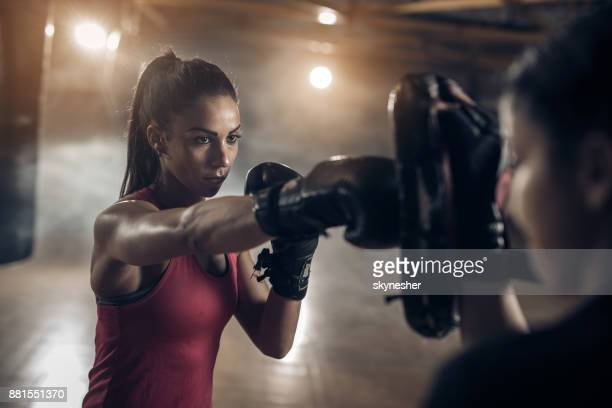 Woman exercising with a coach on a boxing training in a health club.