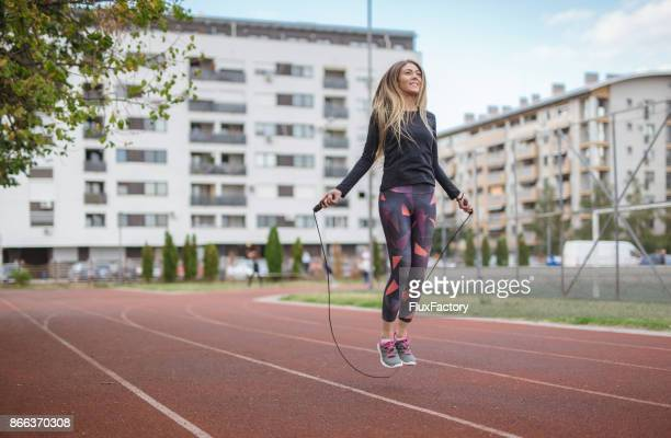 woman exercising with a jump rope - skipping rope stock pictures, royalty-free photos & images