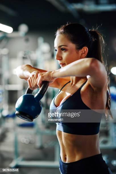 woman exercising with a kettlebell in gym - スポーツトレーニング ストックフォトと画像