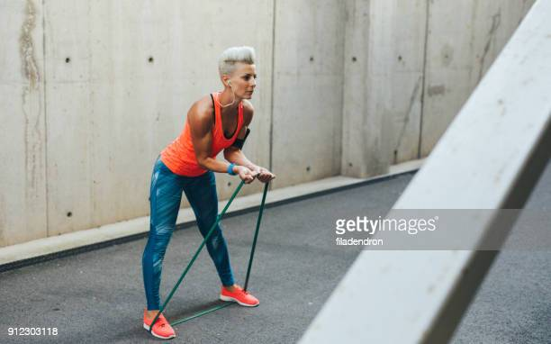 woman exercising with a resistance band - train band stock photos and pictures