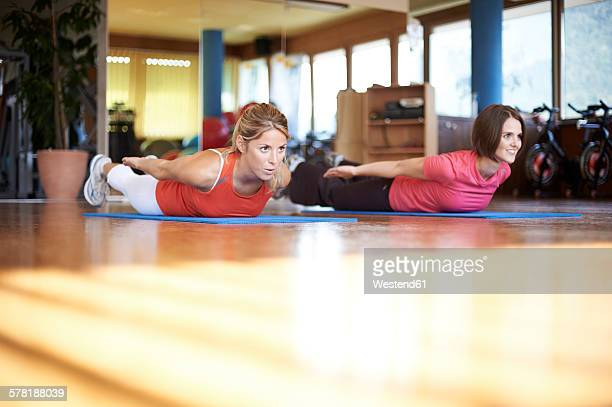 Woman exercising with coach in fitness studio
