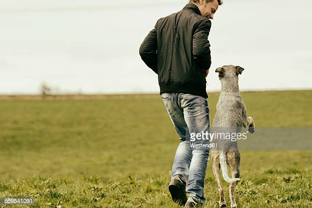 Woman exercising with dog on meadow