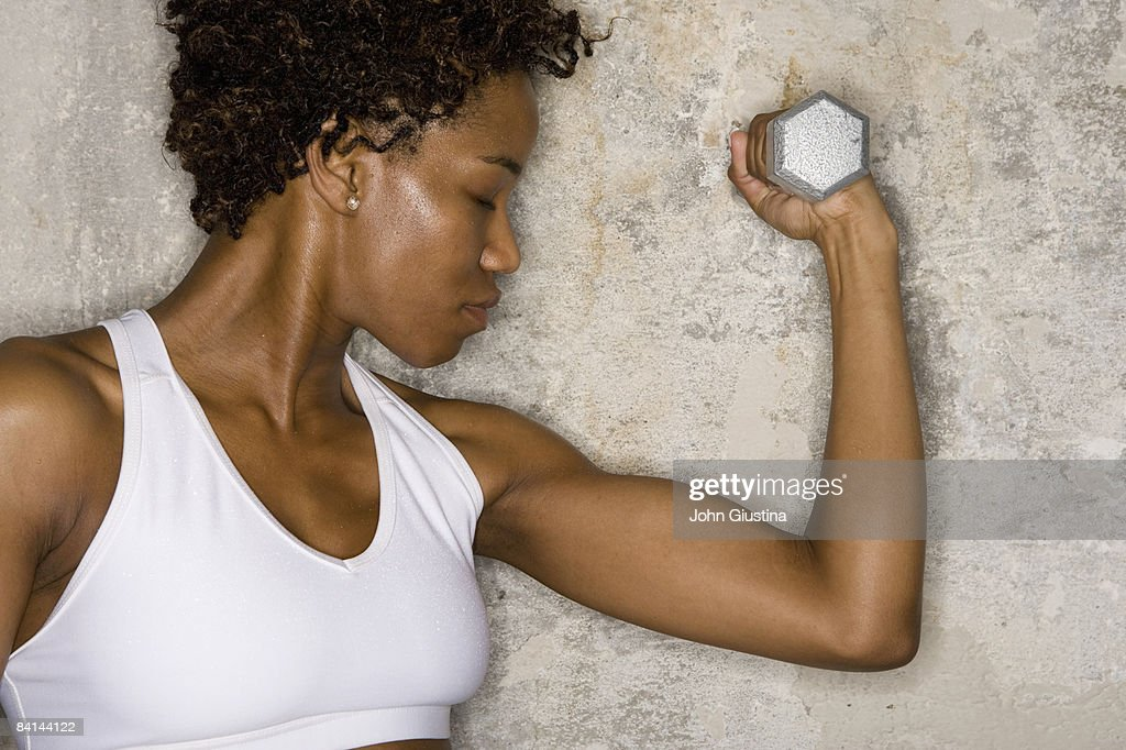 Woman exercising with dumbbell  : Stock Photo