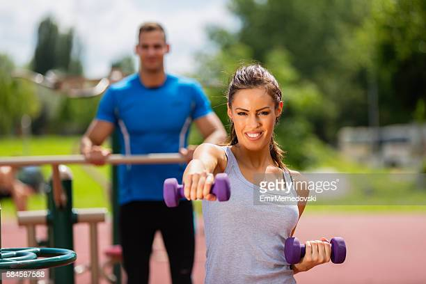 Woman exercising with dumbbells at the outdoor gym.