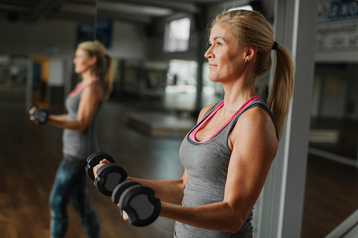 Woman exercising with dumbbells in gym - gettyimageskorea