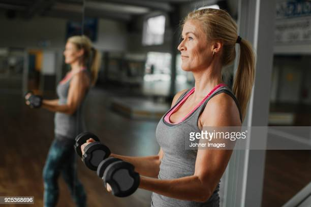woman exercising with dumbbells in gym - musculação com peso - fotografias e filmes do acervo