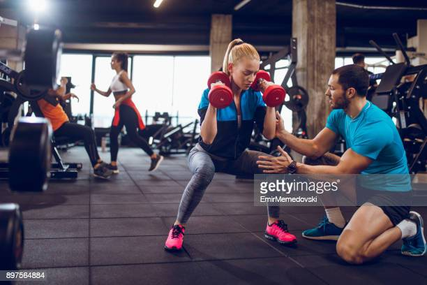 woman exercising with dumbbells in squat position - fitness instructor stock pictures, royalty-free photos & images