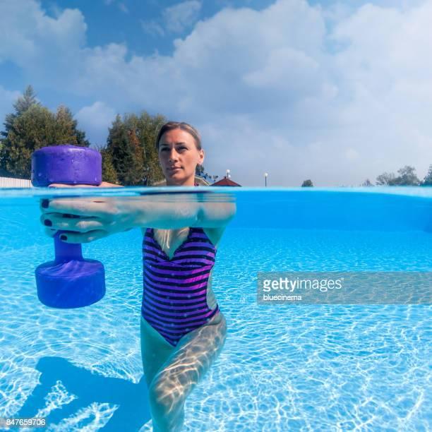Femme exercice avec des haltères en piscine