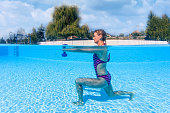 woman exercising with dumbbells swimming pool