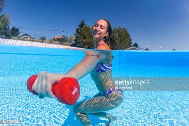 Mujer haciendo ejercicio con pesas en la piscina