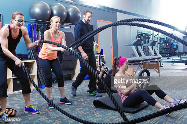 Woman Exercising with Fitness Coach in Weight Training Gym Class