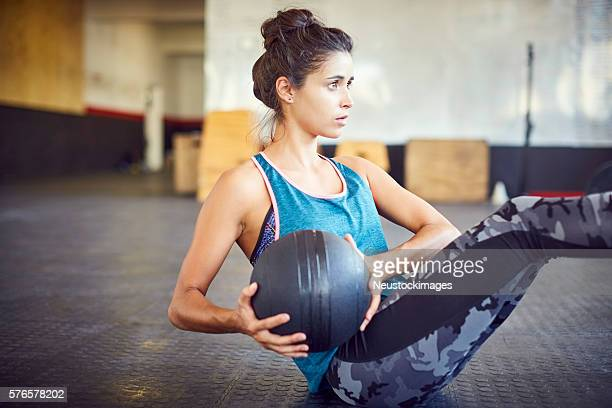 woman exercising with medicine ball in gym - medicine ball stock pictures, royalty-free photos & images