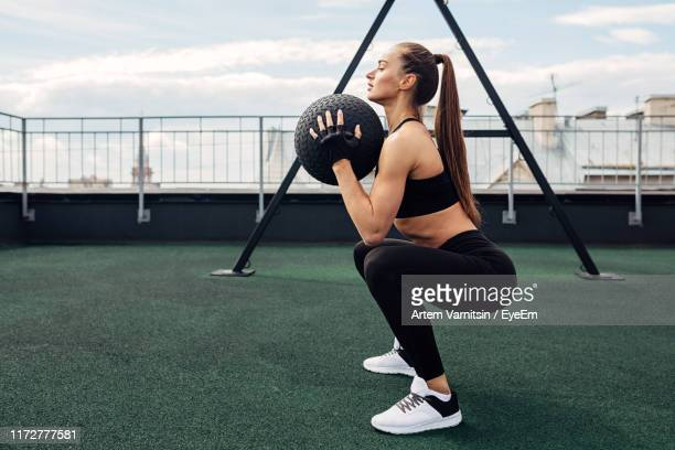 woman exercising with medicine ball - squatting position stock pictures, royalty-free photos & images