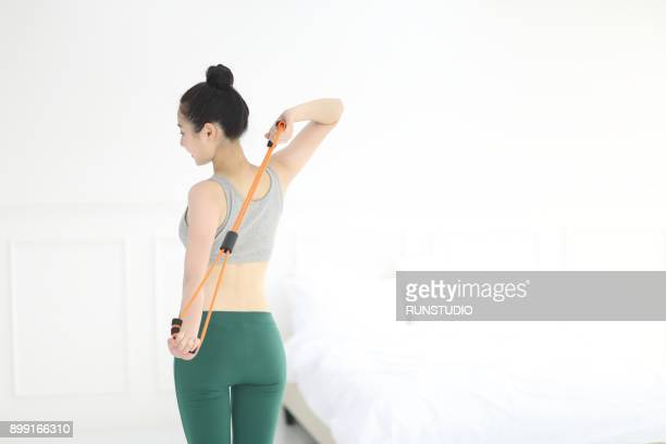 woman exercising with residence band in bedroom - ブラトップ ストックフォトと画像