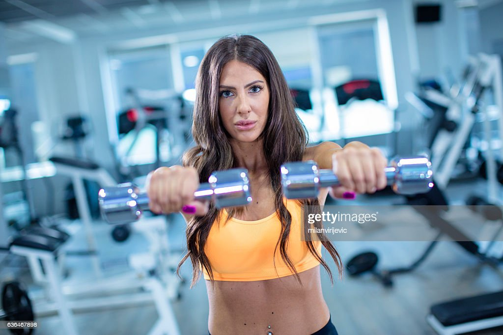 Woman exercising with set of weights : Stock Photo