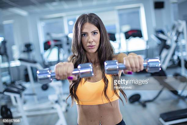 woman exercising with set of weights - mid section stock photos and pictures