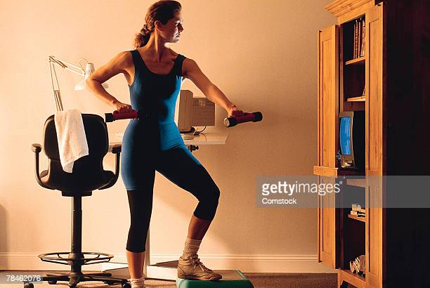 Woman exercising with television at home