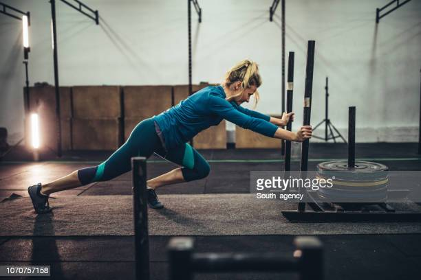 woman exercising with weights in the gym - cross training stock pictures, royalty-free photos & images