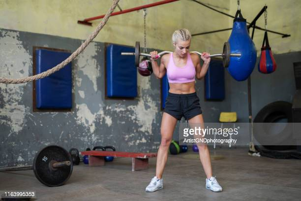 woman exercising with weights - women's weightlifting stock pictures, royalty-free photos & images