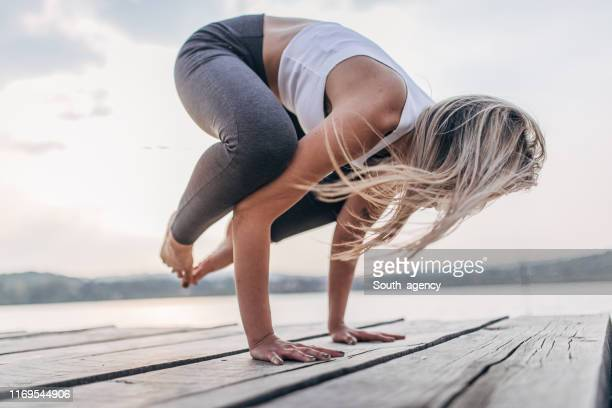 woman exercising yoga by the lake - handstand stock pictures, royalty-free photos & images