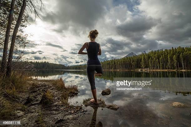 Frau Ausübung yoga by the lake