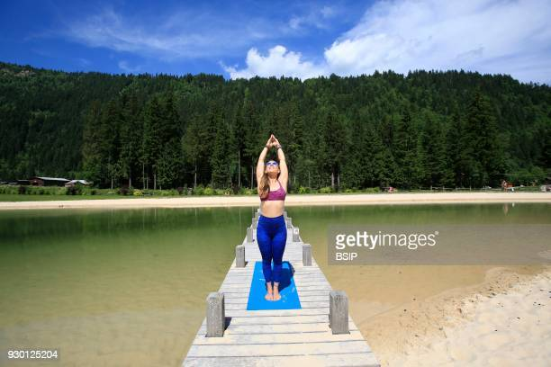 Woman exercising yoga on jetty Les Contamines France