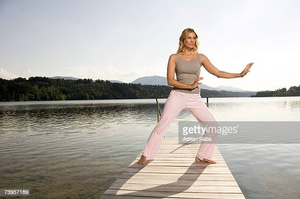 Woman exercising tai chi on jetty