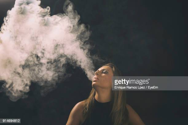 Woman Exhaling Smoke Against Wall